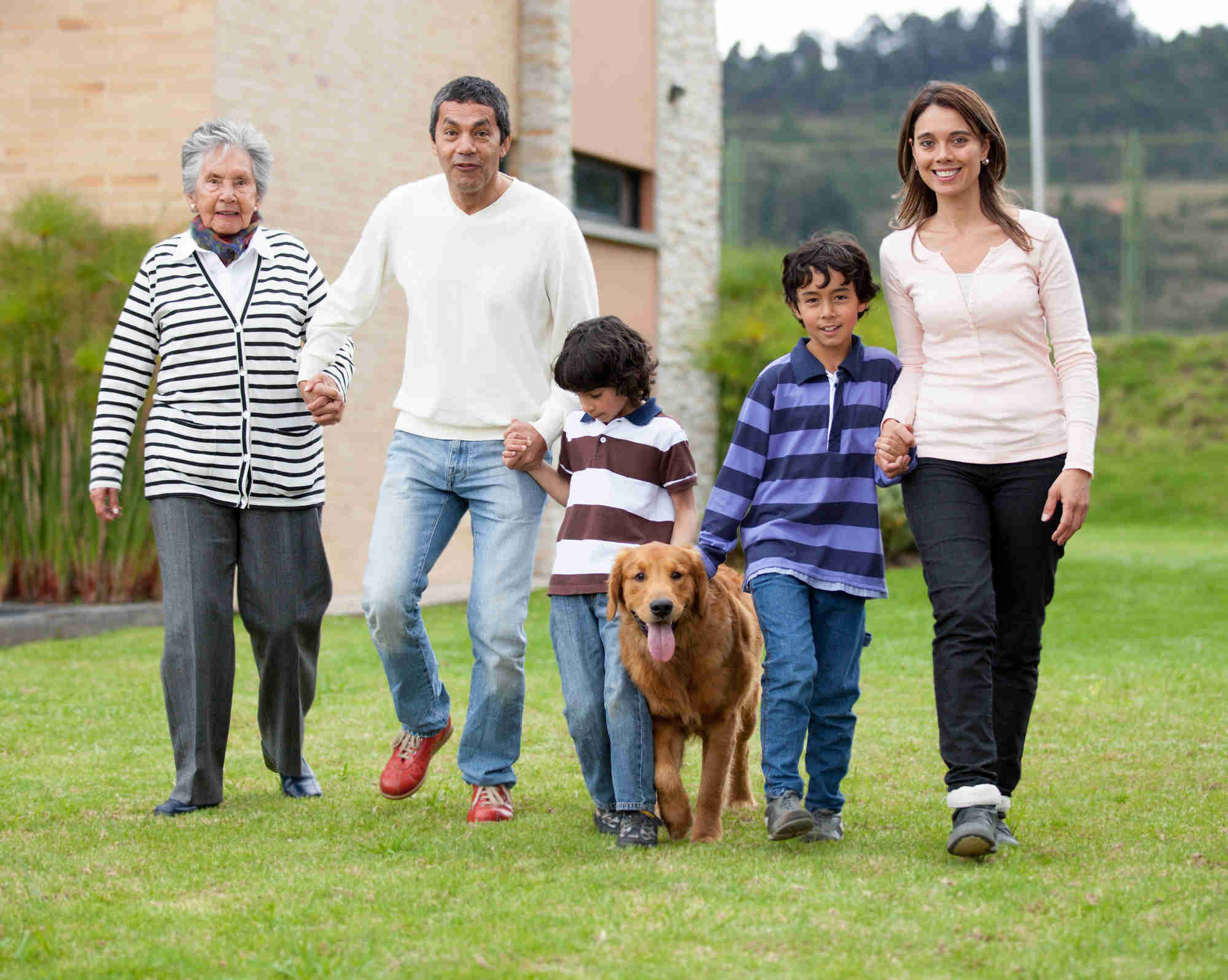 Beautiful family walking outdoors with a dog and smiling